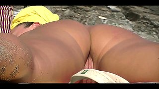 Beach voyeur spies on a busty mom with a tight shaved cunt