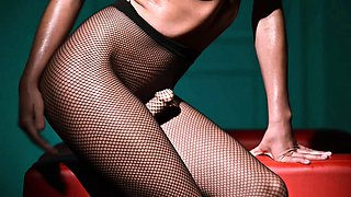 Tiffany strides into a bare  blue it room wearing fishnet