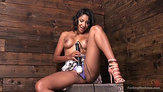 Darker tanned woman rams herself with a dildo machine