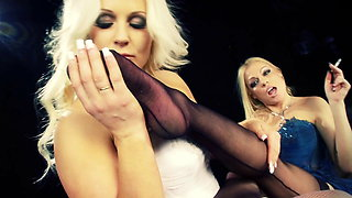 Playful blondes touch each other and kiss while smoking